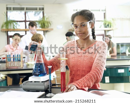 Pupils doing science experiments at desks in classroom, focus on teenage girl (15-17) in foreground - stock photo