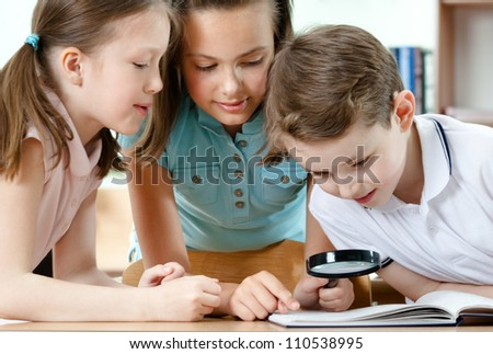 Pupils examine something in the book through the loupe - stock photo