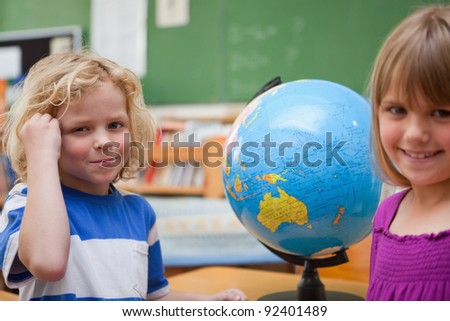 Pupils posing in front of a globe in a classroom