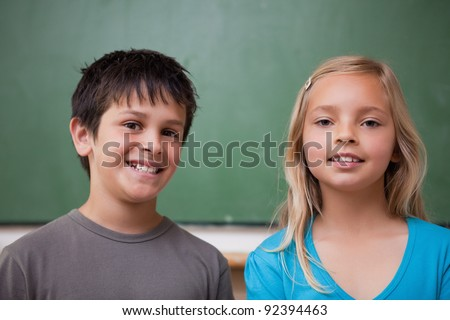 Pupils posing together in front of a chalkboard - stock photo