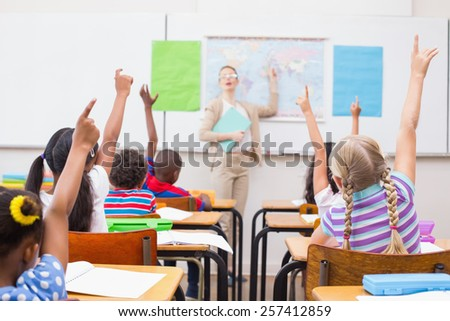 Pupils raising hand during geography lesson in classroom at the elementary school - stock photo