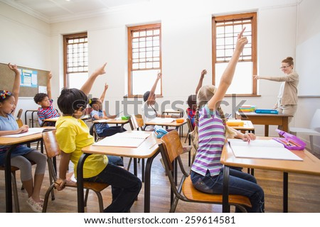 Pupils raising hand in classroom at the elementary school - stock photo