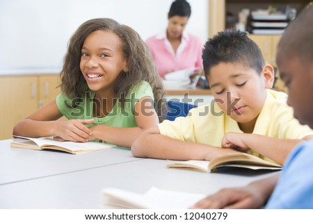 Pupils reading whilst sitting at desks - stock photo