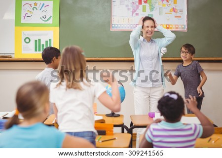 Pupils running wild in classroom at the elementary school - stock photo