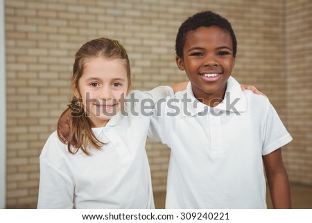 Pupils smiling with arms around each other in elementary school