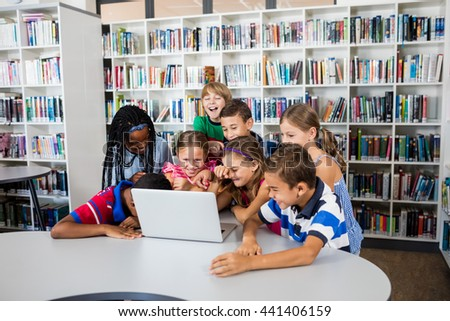 Pupils studying with laptop in library - stock photo
