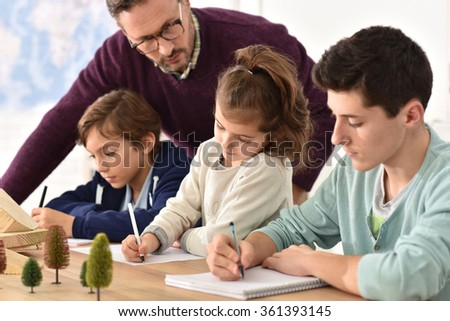 Pupils taking notes during science class - stock photo