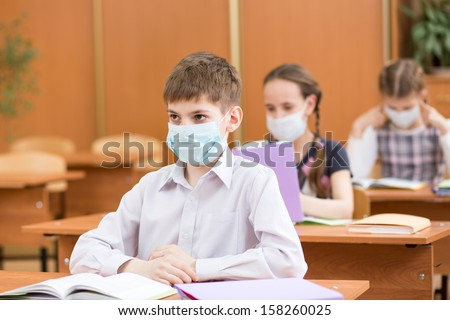 pupils with protection mask against flu virus at lesson - stock photo
