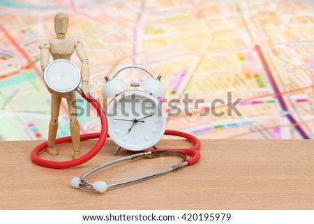 puppet doll ,stethoscope and clock on desk with blur road map background - stock photo