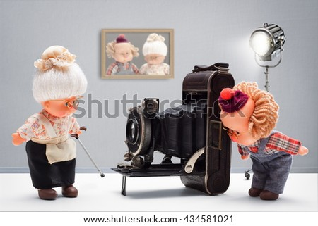 Puppets of senior photographer taking, with passion until the end, pictures of his old ladies with vintage camera in his studio - stock photo