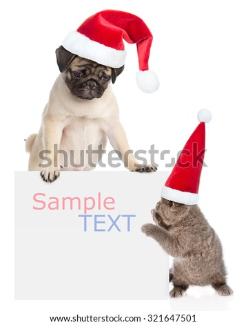 Puppy and kitten with red Santa Claus hats peeking from behind empty board. isolated on white background - stock photo