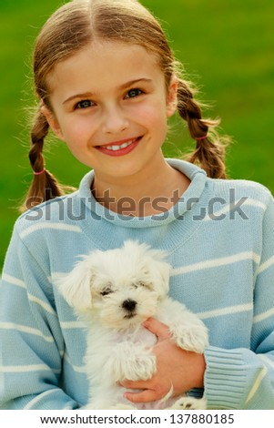 Puppy, child - lovely girl playing with cute puppy in the garden, best friends - stock photo