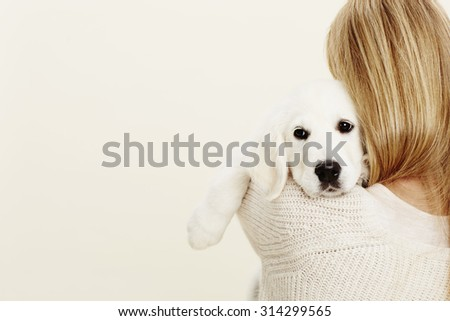 Puppy embraced by blonde owner, studio - stock photo