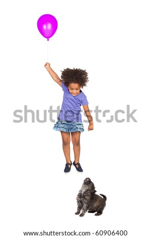 Puppy girl looking at a fly with a balloon isolated over white - stock photo