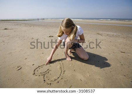 puppy love, girl drawing a heart in the sand at the beach - stock photo