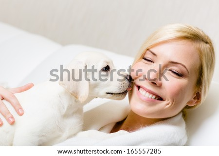 Puppy of labrador licking the face of woman sitting on the white leather sofa - stock photo