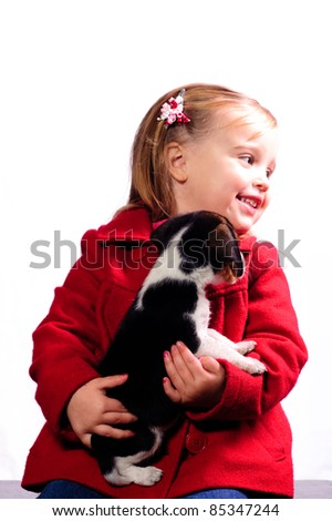 puppy trying to lick a small girl - stock photo
