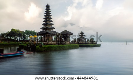 Pura Ulun Danu Bratan , a Hindu temple in the evening of a rainy day of summer in Bali, Indonesia. Long exposure, image stack. Boat can be seen in foreground. Perspective corrected.   - stock photo