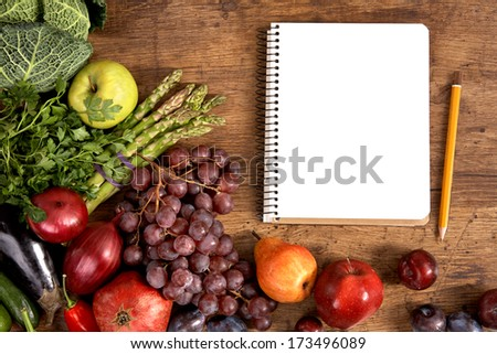 Purchase list. Empty space / studio photography of open blank ring bound notebook surrounded by a fresh vegetables and pencil on old wooden table  - stock photo