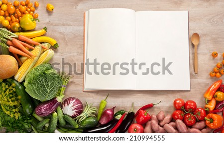 Purchase list. Shopping List. Cookbook. Cookery book. Copy space / food photography of open blank notebook surrounded by a fresh vegetables on wooden table  - stock photo