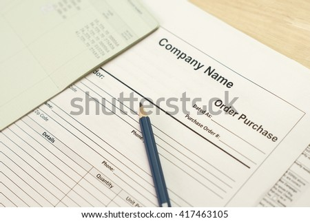 purchase order paper form with pencil and account book, selective focus