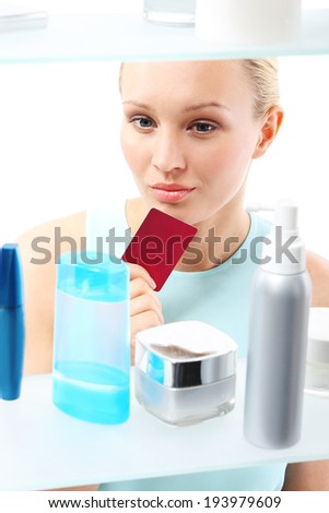 Purchases on credit .Woman buying cosmetics in drugstore  A woman with a card club buys cosmetics  - stock photo
