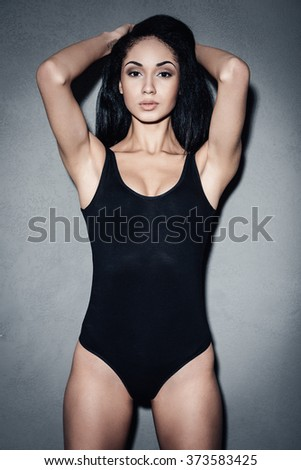 Pure beauty. Beautiful young African woman in black swimsuit holding hands in hair and looking at camera while standing against grey background - stock photo