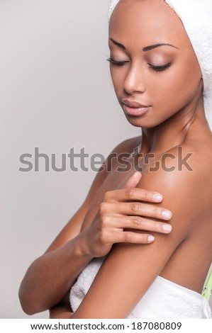 Pure beauty. Beautiful young Afro-American shirtless woman touching her face and keeping eyes closed while Isolated on gray background - stock photo