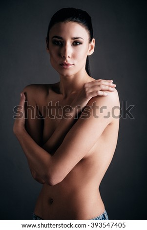 Pure beauty. Beautiful young shirtless woman posing and looking at camera while standing against black background - stock photo
