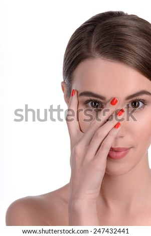 Pure beauty. Young attractive brunette girl covering her face with hand and looking at camera while standing isolated on white background - stock photo
