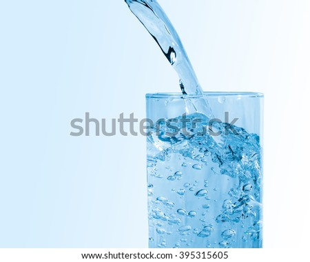 Pure blue water pouring into a glass with bubbles and splash