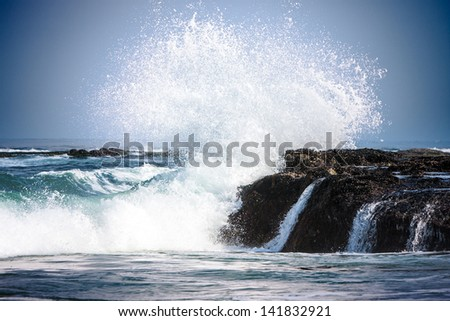 Pure Blue Waters Of California's Pacific Ocean, Coastal Waves Breaking And Splashing On Sea Coast Rocks Encrusted With Mussels - stock photo
