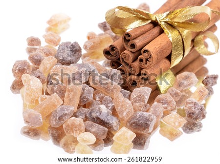Pure cane brown sugar with cinnamon sticks on white background. Macro with extremely shallow dof. - stock photo