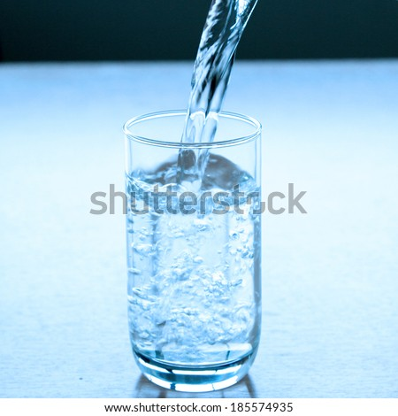 Pure drinking water pour into glass - stock photo