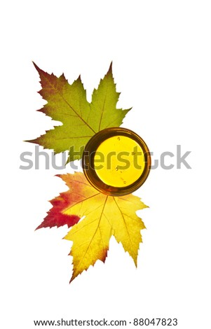 Pure golden maple syrup with colorful  maple leafs on white background - stock photo