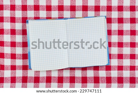 Pure notebook for recording menu on red -white checkered tablecloth  - stock photo