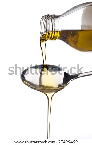 Pure virgin olive oil being poured out of a glass bottle onto a fork - stock photo