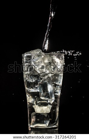 Pure water in glass with artificial ice from resins on black background, splashing of water