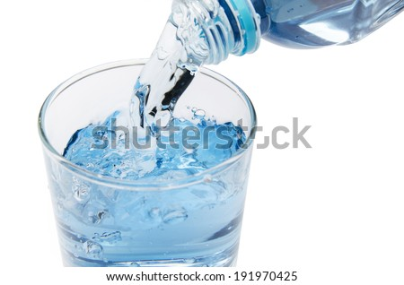 pure water is emptied into a glass of water from bottle. fresh drinking water - stock photo