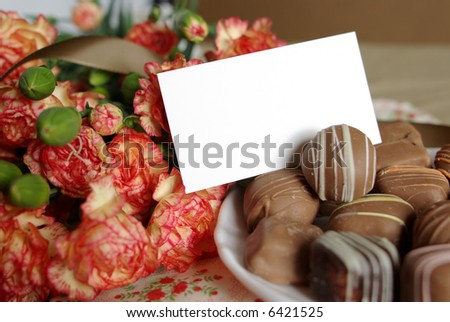 Pure white card surrounded by gourmet chocolates and beautiful flowers.  Ready for your message. - stock photo