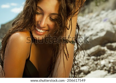 Pure woman beauty with wet hair and bright make up. Smiling beauty . Toned in warm colors. horizontal shot on the beach. - stock photo