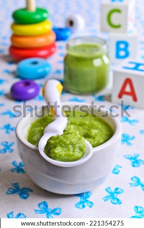 Puree of green in the small bowl is on the background of childrens toys - stock photo