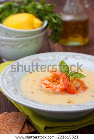 puree soup with vegetables - cauliflower, potatoes and onions with red lentils and shrimp in a blue plate