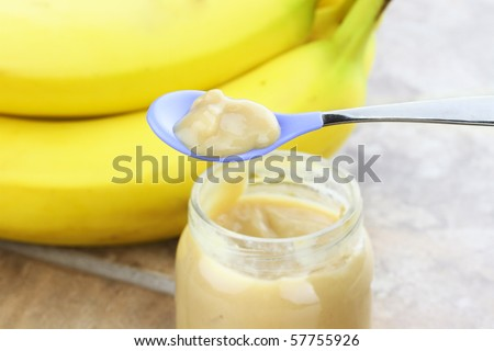 Pureed baby food from a jar with fresh bananas in background. - stock photo
