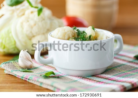pureed vegetable soup with cauliflower in a white plate with greens - stock photo