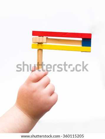 Purim holiday A child's hand holding Colorful wooden noisemaker  - stock photo