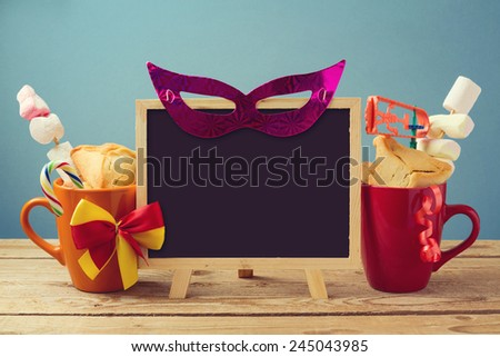 Purim holiday background with chalkboard and traditional gifts - stock photo