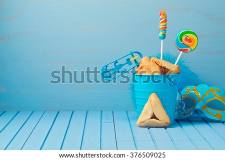 Purim traditional gifts with hamantaschen cookies, noisemaker and carnival mask on blue background - stock photo