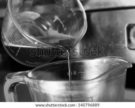 puring espresso coffee to glass, monotone color