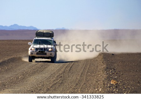 PUROS, NAMIBIA, JANUARY 10: 4x4 prepared off-road car driving in the Kaokoland Desert with blue sky and load of dust behind the car. Namibia 2010 - stock photo